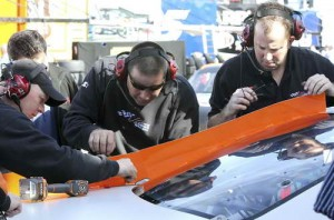 Crew members of the #20 Home Depot Toyota make adjustments to the deck spoiler during Daytona Preseason Thunder at Daytona International Speedway